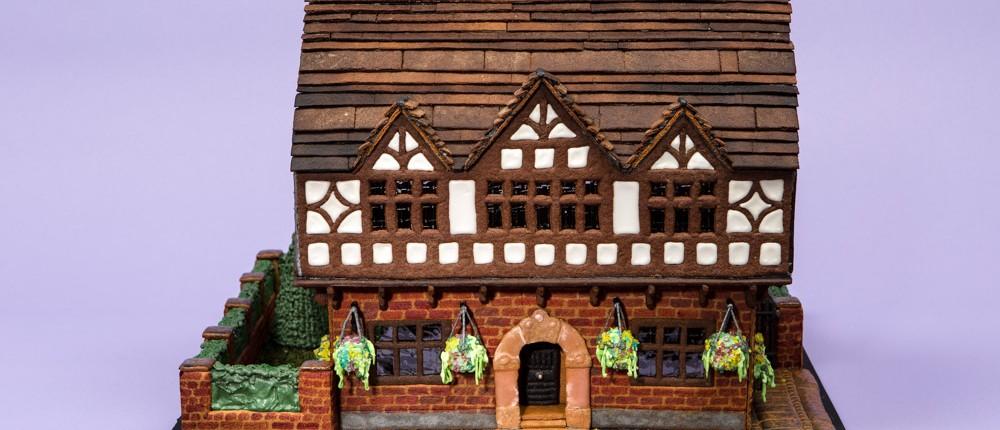 Ett pepparkakshus i form av engelskt korsvirkeshus med trädgård och tegelmur.