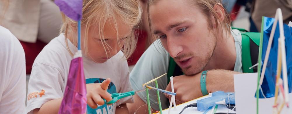 Familjeaktivitet på ArkDes. Litet barn bygger med pappersrör och limpistol. Vuxen man är med bredvid.