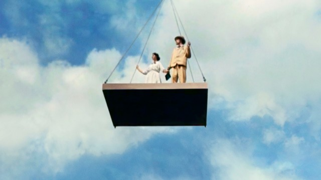A man and a woman standing on a flying concrete panel., held by a crane.